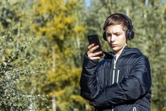 The guy listens to music on headphones and looks into his phone on a sunny autumn day against the background of trees. Royalty Free Stock Photography