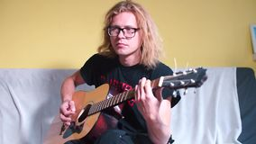 A guy with long hair plays an acoustic guitar. Adjusts the sound, twists the tunes stock video