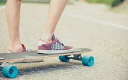 Guy on longboard. Close-up image of male legs on longboard on road in summer Stock Image