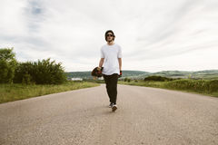 A guy with a longboard in his hands in a helmet and sunglasses is walking along an asphalt suburban road Stock Images