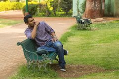 Guy looking away sitting on a bench in a park. Young guy looking away sitting on a bench in a park Royalty Free Stock Photography
