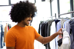 Guy looking at clothes in store. Young guy looking at clothes in store Royalty Free Stock Images