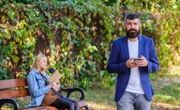 Guy looking for girlfriend. Dating application concept. Application for search partner romantic relations. Man with. Beard hold smartphone while girl sit bench royalty free stock photography