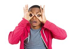 Guy looking through his fingers like binoculars Stock Photography