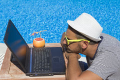Guy looking at laptop screen at the poolside Royalty Free Stock Image