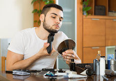 Guy looking at mirror and shaving beard with trimmer Stock Photos