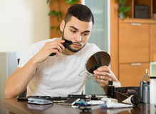 Guy looking at mirror and shaving beard with trimmer Royalty Free Stock Image