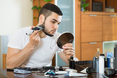 Guy looking at mirror and shaving beard with trimmer Royalty Free Stock Photo