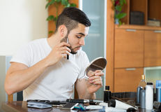 Guy looking at mirror and shaving beard with trimmer Stock Image
