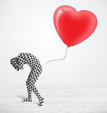 Guy looking at a red balloon shaped heart Stock Photo