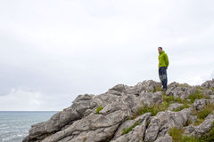 Guy looking at the sea from the rock Stock Photos
