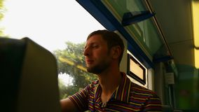Guy looking through window on train, young man traveling by railway transport. Stock footage stock video footage