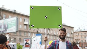 Guy looks atcamera and smiles at the demonstration. The man laughs at rally 4k. Smile adult young man with a banner in hands go and shouts loudspeaker rally stock footage
