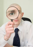 Guy looks through the big magnifier Stock Images
