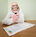 Guy looks through the big magnifier Royalty Free Stock Image