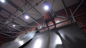 A man in an orange sweatshirt and a helmet performs on rollers a trick invert, slow motion stock video