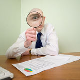 Guy looks through the magnifier Stock Images