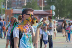 The guy looks at smartphone. The festival of colors Holi in Cheboksary, Chuvash Republic, Russia. 05/28/2016 Royalty Free Stock Image