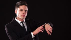 The frowning guy points at the wristwatch on his wrist stock photo