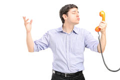 A guy in love holding a telephone tube and giving kisses Stock Images