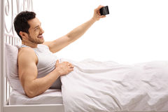 Guy lying in bed and taking a selfie Royalty Free Stock Image