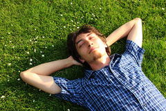 A guy lying on a grass field Royalty Free Stock Photography