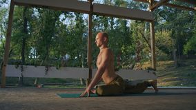 Guy Makes Asanas novo da ioga que senta-se no tapete com o torso despido no Pomo de madeira no parque da cidade filme