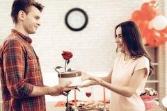 Guy Makes ein Geschenk zur Freundin an Valentinsgruß ` s Tag lizenzfreie stockfotos