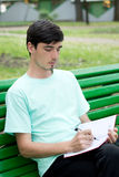 Guy makes entry in a notepad. The young man sits on a shop and makes entry in a notepad Stock Images