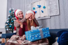 The guy makes the girl a surprise, closing her eyes and presenting a gift-box. Christmas atmosphere. Indoors. Royalty Free Stock Photos