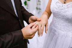 The guy makes an offer to marry his beloved girl, wears a ring. close-up. The guy makes an offer to marry his beloved girl, wears a ring Royalty Free Stock Photos