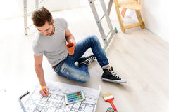 Guy making mark on apartment plan royalty free stock photography