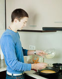 Guy making scrambled eggs in frying pan Royalty Free Stock Photo
