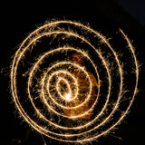 Guy making a spiral with sparkling fireworks. Guy forming a spiral with sparkling bengal fireworks Royalty Free Stock Photos