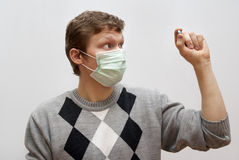 The guy in the mask considers pill. Grey background Stock Image