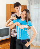 Guy measuring bust of  girlfriend with measuring tape Royalty Free Stock Images