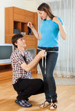 Guy measuring girlfriend with measuring tape Royalty Free Stock Image