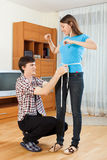 Guy measuring waist of girl Stock Photo