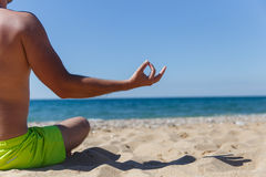 Guy meditating in sandy beach Royalty Free Stock Images