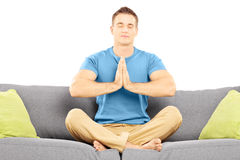 Guy meditating seated on a sofa Royalty Free Stock Image