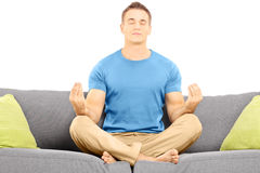 Guy meditating seated on a sofa Stock Photography