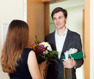 Guy meet his young woman with flowers Royalty Free Stock Images
