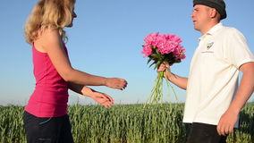 Guy meets country woman. Rural guy meets a young countrywoman handed her a large bouquet and embraced stock video footage