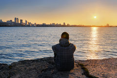 The guy meets the sunset siting on the river bank Royalty Free Stock Photography