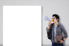 Guy with megaphone and blank board. Guy announcing something with megaphone and blank board for copy space Stock Photo