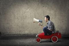 Guy with a megaphone in a toy car Stock Photo
