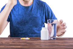 A guy with a migraine. Suicide prevention. A man taking meds isolated on a white background. A sick male in a blue t-shirt. Stock Image