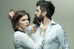 Guy with modern hairstyle visiting hairdresser. Barbershop or hairdresser concept. Woman hairdresser cuts beard with Stock Images