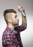 Guy with mohawk putting hairspray. Royalty Free Stock Photos