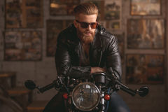 Guy in motorbike repair shop. Handsome bearded man in leather jacket and sun glasses is sitting on the motorcycle in the repair shop Royalty Free Stock Photography